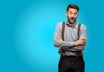 Middle age man, with beard and bow tie nervous and scared biting lips looking camera with impatient expression, pensive