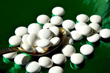 таблетки белого цвета лежат на ложке из золота на зелёном фоне