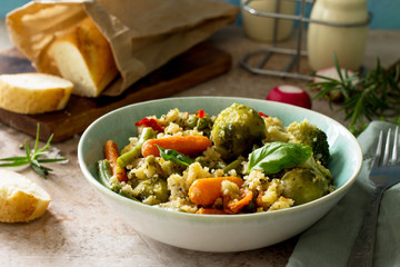 Healthy proper nutrition. Dietary vegan dish: couscous and vegetables (string beans, brussels sprouts, carrots, sweet peppers, tomatoes) on a stone or slate background.