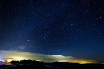 Starry sky above the clouds. Clouds are illuminated by lanterns.