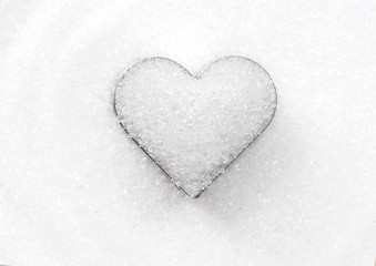 Heart shape by white granulated sugar on the pile sugar background for valentines day and love element concept design.