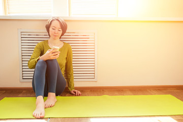 cheerful brunette woman in green blouse holds a roll of mate and looks into the phone near the window in a yoga class. smartphone in the hands of a yoga coach