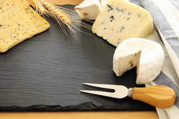 image of dairy products over black stone slate background. Symbols of jewish holiday - Shavuot.