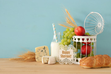 image of fruits, bread and cheese in decorative basket over wooden table.