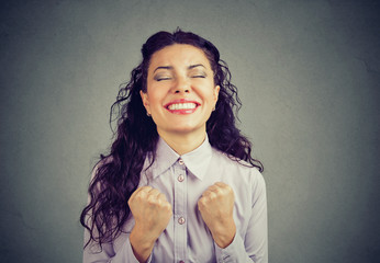 successful woman winning with fists pumped celebrating success