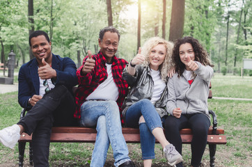 Multiethnic group of happy young people sitting and showing ok gesture