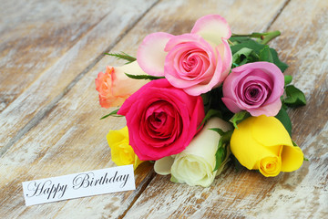 Happy Birthday card with colorful bouquet of roses on rustic wood