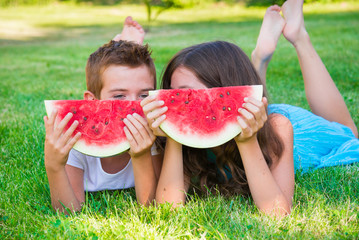 Two children eating juicy watermelon outdoors on grass