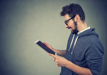 man using tablet looking at screen