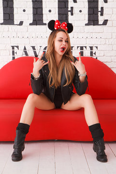 Beautiful sexy girl in black bodysuit, black leather jacket and Mickey Mouse Ears with red bow