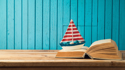 Boat and book on wooden table