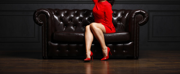 Girl in red dress sitting on the couch
