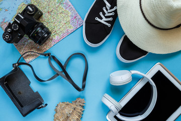 Travel accessories camera, straw hat, card, shoes on a blue background flat top view layout with copy space