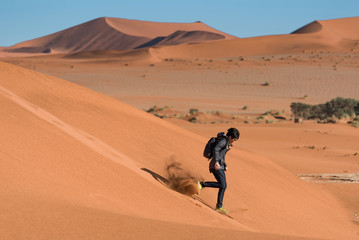 Young Asian man dress in black and carrying backpack running down on sand dune in Namib desert of Namibia, Africa
