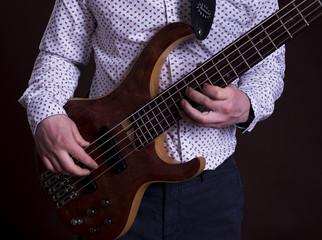 Close up shot of the man playing electric bass guitar