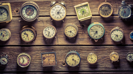 Mix of aged clocks on the wooden wall