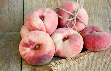 Saturn peach or Dough nut peaches on wooden background and sack cloth
