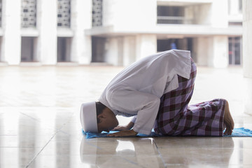Muslim religious man doing Salat in the mosque