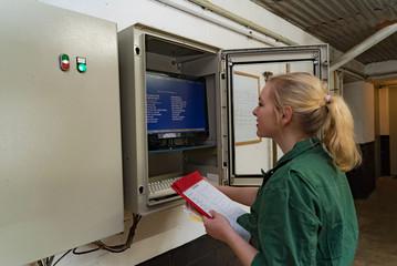 Mechanisierung ín der Schweinehaltung, junge Landwirtin kontrolliert die EDV