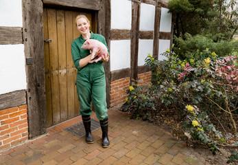 Junge Landwirtin in Arbeitskleidung vor Fachwerkspeicher hält Ferkel im Arm