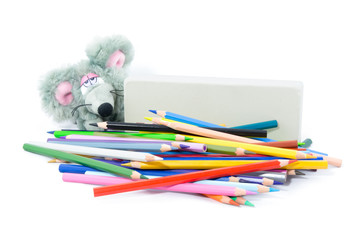 Set of colored pencils, big eraser and grey toy mouse. Isolated on white background