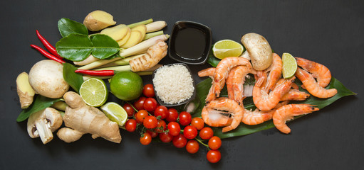 Special ingredients for popular Thai spicy soup Tom-yum kung lime, galangal, red chili, cherry tomato, lemongrass and kaffir lime leaf on black table with copy space. View from above.