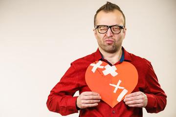 Adult man holding broken heart