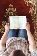 Muslim man reading Islamic holy book quran