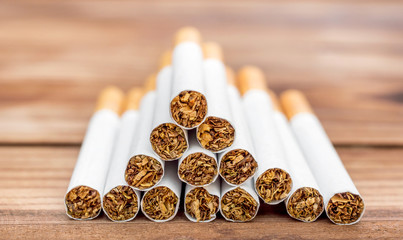 Heap of cigarettes on wooden table.