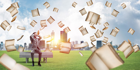 Many old books falling from above and student guy sitting on bench