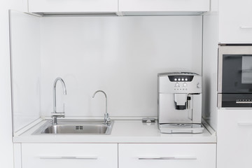Metal chrome sink with two taps, plain and filtered water. Fragment of modern kitchen with counter and sink. Detail of interior apartment.