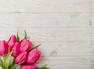 Bouquet of pink tulips on a light wooden background. View from above.