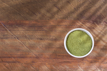 Organic moringa powder on wooden background - Moringa oleifera