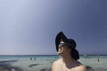 Man stood on the beach wearing straw black hat. Outdoor portrait of smiling young man on the beach.