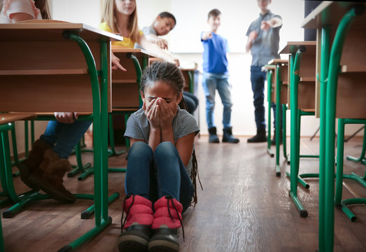 Bullied African American girl sitting on floor in classroom
