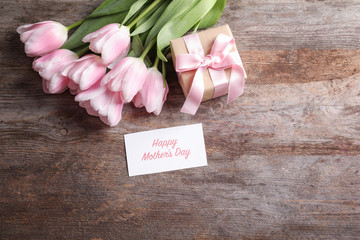 Greeting card with text HAPPY MOTHER'S DAY, tulips and gift box on table, top view