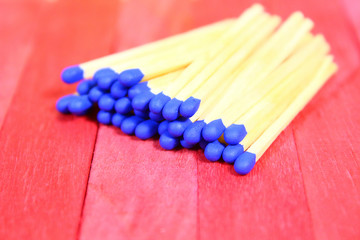 A pile of matches with a blue head on a red wooden surface. Isolated. Close-up.