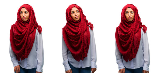 Arab woman wearing hijab making funny face fooling isolated over white background