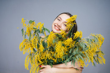 happy young girl holding a big bouquet of a fragrant yellow mimosa, smiling