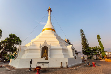 Golden light shining on white and gold pagoda during sunrise / sunset with blue sky in Mae hong son Thailand