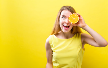 Happy young woman holding a half orange on a yellow background