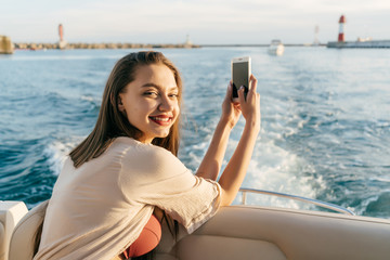 happy young girl swims on her white yacht by the sea, holds a smartphone and smiles