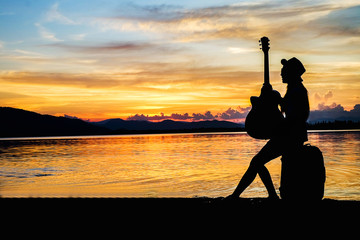 woman traveler have baggage and guitar sitting and looking for view of lake mountain and sunset near the dam on vacation.silhouette concept.