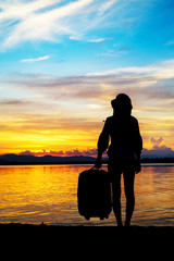 woman traveler have baggage and guitar standing and looking for view of lake mountain and sunset near the dam on vacation.silhouette concept.