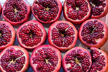 Pomegranate background.Group Opened half pomegranates with beautiful red fleshy seeds. Healthy food concept.