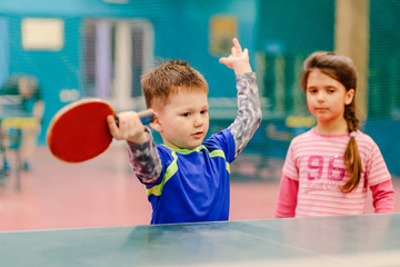 little boy standing in the tennis hall, spreading his hands to the sides. tennis hall, tennis racket, table tennis