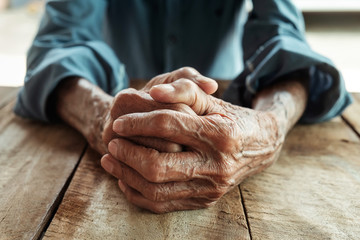 close up of elderly oldman hands on wooden table