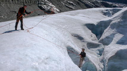 two mountain climbers training their crevasse rescue skills on a glacier in the Alps