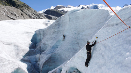 two mountain guide candidates training ice axe and rope skills on a glacier in the Swiss Alps