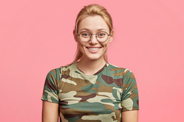 Beautiful blonde cheerful female wears camouflage t shirt, round spectacles, being in high spirit, smiles joyfully, isolated over pink expression. Attractive young woman expresses positive emotions